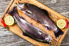 Two raw trouts on a cutting board Royalty Free Stock Photos