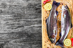 Two raw trouts fishes with lemon slices, hot peppers and salt. On the cutting board, rustic style, horizontal, top view Stock Photo