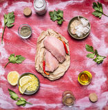 Two raw turkey steak on paper with garlic, grated lemon butter, parsley various spices on wooden rustic background top view Stock Photos