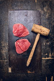 Two raw  veal meat schnitzel  with old meat hammer on dark rustic background Stock Photography