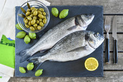 Two ready to cook raw fish with lemon and olives on stone slate. Board. With copy space. Top view Royalty Free Stock Photos