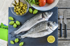 Two ready to cook raw fish with lemon and olives on stone slate. Board. With copy space. Top view Stock Image