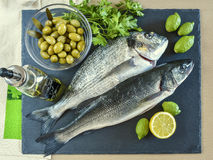Two ready to cook raw fish with lemon and olives on stone slate Royalty Free Stock Image