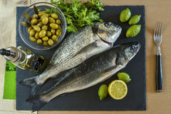 Two ready to cook raw fish with lemon and olives on stone slate. Board. Top view Royalty Free Stock Image