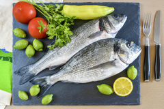 Two ready to cook raw fish with lemon and tomatoes on stone slat. E board. Top view Stock Images