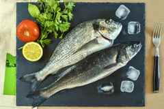 Two ready to cook raw fish with vegetables on stone slate board. Top view Stock Photography