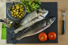 Two ready to cook raw fish with vegetables on stone slate board. Top view Royalty Free Stock Photo