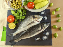 Two ready to cook raw fish with vegetables on stone slate board. Stock Photo