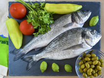 Two ready to cook raw fish with vegetables on stone slate board. Top view Stock Photos