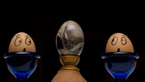 Two real hand-painted eggs look in amazement at a stone egg of volcanic origin against a black background stock image