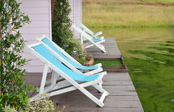 Two Recline chairs on dock facing a green lake. Stock Photo
