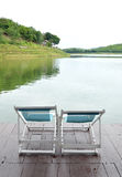 Two Recline chairs on dock facing a green lake. Stock Photography