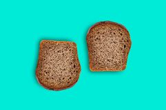 Two rectangular pieces of fresh rye bread in center of green table on kitchen. Top view royalty free stock photography