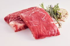 Two rectangular portions of raw lean flank steak. With fresh garlic cloves and a bouquet garni with fresh herbs including rosemary and thyme royalty free stock photo