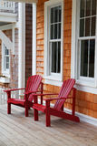 Two red Adirondack chairs. On a wood deck against a brown wood shake home Royalty Free Stock Image