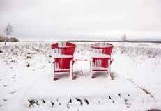 Two red Adirondack chairs on snowy field Royalty Free Stock Photos