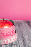 Two red apple with measuring tape on pink background. Healthy diet concept. Royalty Free Stock Image
