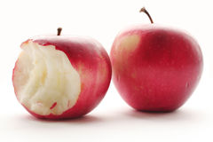 Two red apples. One whole and one bitten over white background Royalty Free Stock Photography