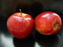 Two red apples on a black background Royalty Free Stock Photography