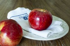 Two red apples , one of them focused on white napkin of yarn on a wooden backgroun royalty free stock photo