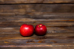 Two red apples on a wooden background. Two red, ripe apples on a wooden background close up Royalty Free Stock Photos
