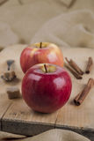 Two red apples on wooden board and spices. Lady Alice type apples, cinnamon, sugar in spoon on wooden surface Stock Photography