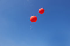Two red balloons flying in a blue sky. Two red balloons flying in a bright blue sky royalty free stock images
