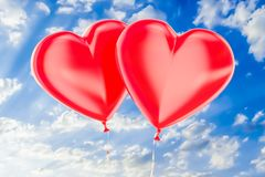 Two red balloons in the shape of hearts flying on a blue sky, 3D. Two red balloons in the shape of hearts flying on a blue sky Stock Photography