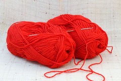 Two red balls (clews) of yarn and knitting hook Stock Photos