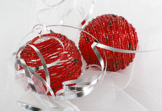 Two red beaded christmas ornaments with silver ribbon. Two red beaded glass christmas ornaments with silver ribbon and white mesh Royalty Free Stock Images