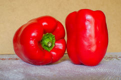 Two red bell peppers. On table Royalty Free Stock Photos
