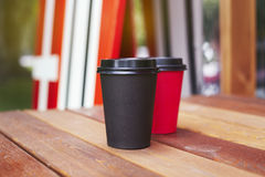Two red and black paper cups to takeaway on wooden floor outside the cafe. Surfing boards stand behind at the background. Stock Photos