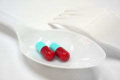 Two red and blue capsules on plastic spoon fork Stock Photography
