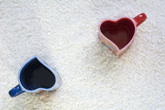 Two red and blue cups in form of heart apart Royalty Free Stock Photography