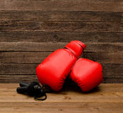 Two red boxing gloves lie on a wooden brown background, skipping rope empty space Royalty Free Stock Photos