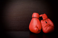 Two red boxing gloves on the side of the frame on a black background Stock Photography