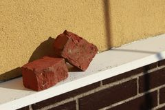 Two red bricks on brick wall`s ledge royalty free stock photography