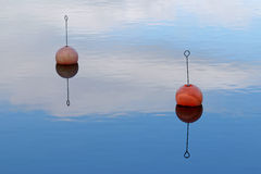 Two red buoy reflecting in calm water Royalty Free Stock Image
