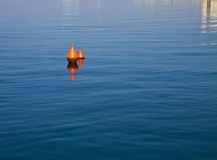 Two red buoys floating on blue waters Royalty Free Stock Photos