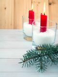 Two red burning candles in the glasses and blue spruce branches Royalty Free Stock Images