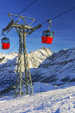 Two red cabins of cable railway on winter sport resort in swiss Royalty Free Stock Photo