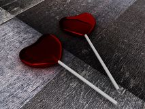 Two red candies on a stick on wooden background Stock Image