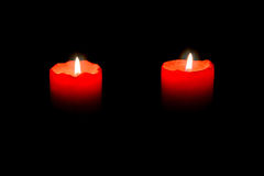 Two red candles burning in the darkness Stock Photos