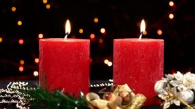 Two red candles with christmas decorations on. Two big red candles with christmas decorations on black background, bokeh, light, garland stock footage