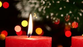 Two red candles with christmas decorations on. Two big red candles with christmas decorations on black background, bokeh, light, garland, cam moves to the right stock video footage