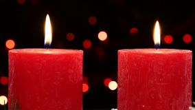 Two red candles with christmas decorations on. Two big red candles with christmas decorations on black background, bokeh, light, garland, cam moves top down stock video footage
