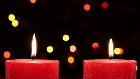 Two red candles with christmas decorations on. Two big red candles with christmas decorations on black background, bokeh, light, garland, dynamic change of focus stock footage