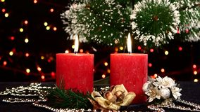 Two red candles with christmas decorations and. Two big red candles with christmas decorations and tree on black background, bokeh, light, garland stock video