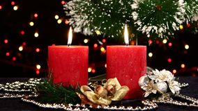 Two red candles with christmas decorations and. Two big red candles with christmas decorations and tree on black background, bokeh, light, garland, rotation stock video footage