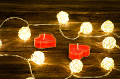 Two red candles in the shape of a heart and glowing lanterns made of rattan on a wooden background. Close-up Royalty Free Stock Images
